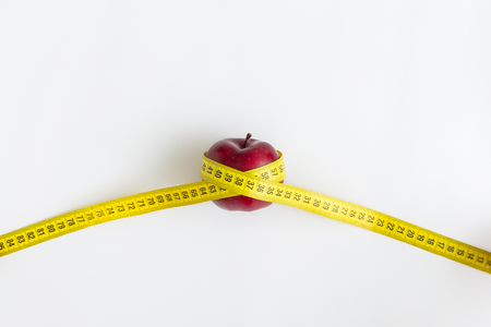 Dieting concept. Red apple with yellow measuring tape isolated on white
