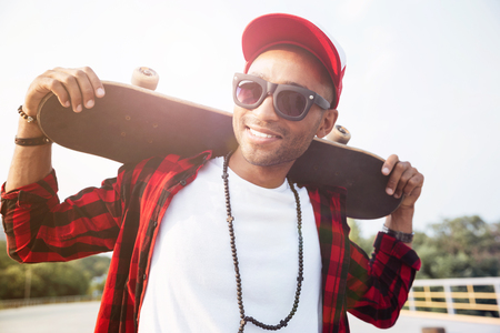 Photo of young dark skinned man wearing sunglasses holding skateboard. Against the nature background. Stock Photo