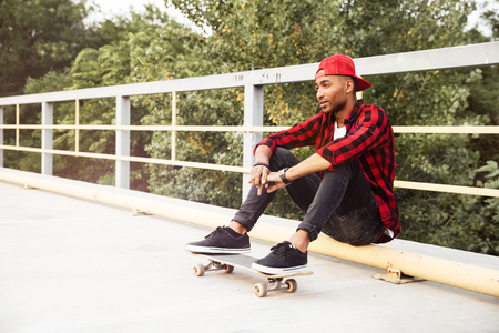 Picture of young dark skinned man wearing sunglasses and cap sitting with his skateboard. Against the nature background.