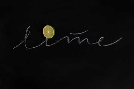 Slice of a fresh green lime with the inscription over black background