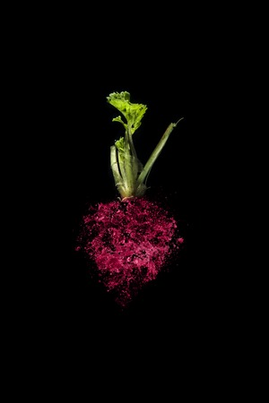 Red beet with water drops isolated on black background