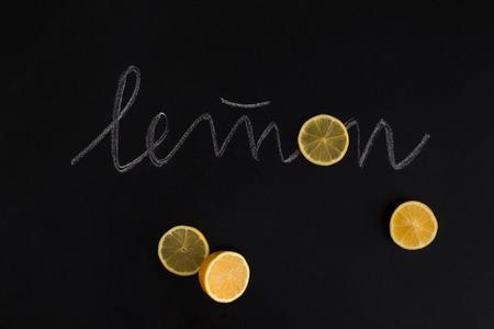 Snijd vers oranje fruit met de inscriptie op zwarte achtergrond Stockfoto