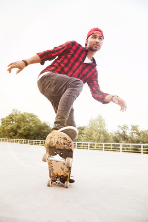 Photo of young dark skinned guy wearing cap skateboarding. Against the nature background. Stock Photo