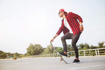 Picture of young dark skinned man wearing sunglasses skateboarding. Against the nature background. Stock Photo