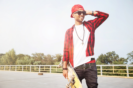 Photo of young dark skinned man wearing sunglasses holding the skateboard. Against the nature background.