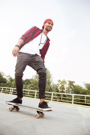 Picture of young dark skinned man wearing sunglasses and cap skateboarding. Against the nature background.