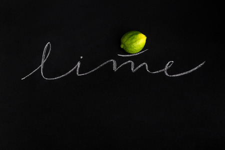Juicy fresh lime with the inscription over black background