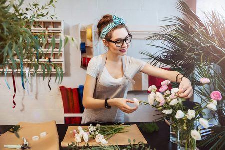 Smiling attractive young woman florist working and making bouquet in flower shop Reklamní fotografie