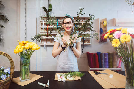 Cheerful amusing young woman florist making bouquet and having fun in flower shop Imagens