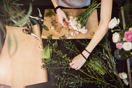 Top view of hands of young woman florist creating bouquet of flowers on black table