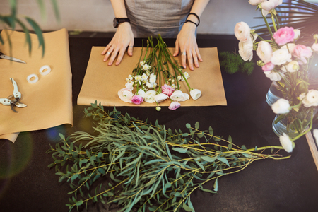 Top view of hands of female florist designing and creating flower bouquet on black table