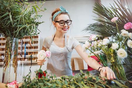 Gelukkige mooie jonge vrouwenbloemist die boeket in bloemwinkel maken Stockfoto