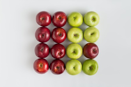 Top view of red and green juicy apples in a row. One red apple in a row with green apples