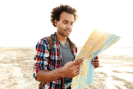 Handsome african young man in plaid shirt with map standing outdoors Stock Photo