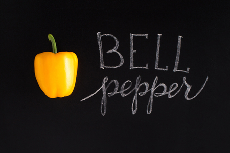 Fresh yellow bell pepper with the inscription over black background Stock Photo