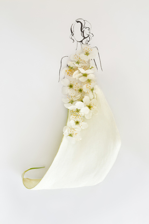 Hand drawn female silhouette wearing dress made of blooming white flowers and petals isolated over white. Fashion illustration Stock Photo