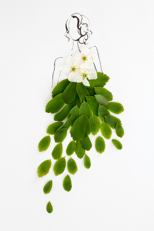 Hand drawn beautiful female silhouette wearing natural floral dress made of green leaves and white flowers isolated over white. Fashion illustration