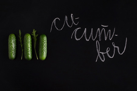 Three fresh raw cucumbers isolated on black background