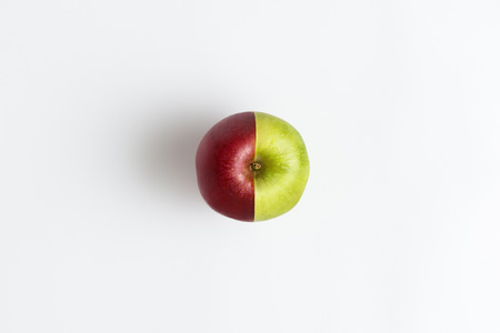 Top view of an apple combined from two half of red and green color isolated Фото со стока