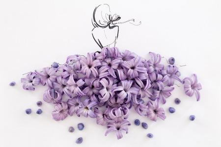ドレスを着て手描かれた女性のシルエットの背面図は白で分離されたヒヤシンス咲く紫花から成っています。ファッション イラスト-