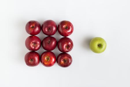 Draufsicht eines grünen Apfels unter roten Äpfeln über Weiß