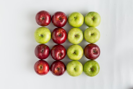 Top view of red and green juicy apples in a row. One red apple in a row with green apples. One green apple in a row with red apples