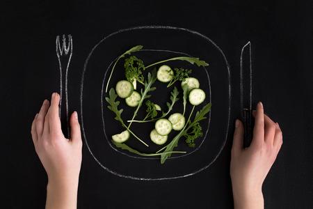 Hände halten gezogenes Messer und Gabel bereit, Salat von einem Teller über schwarzem Hintergrund zu essen Standard-Bild - 84674986