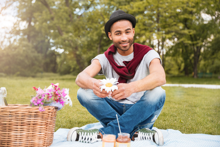Smiling young african american man in hat sitting and having picnic in park