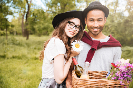 Portrait of happy young couple with basket of drinks, food and flowers standing outdoors