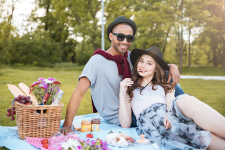 Portrait of happy young couple having rest on picnic in park