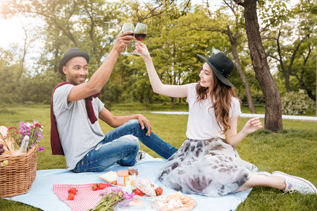 Cheerful young couple drinking wine on picnic in park