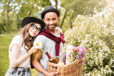 Cheeerful young couple with food and drinks for picnic standing in park