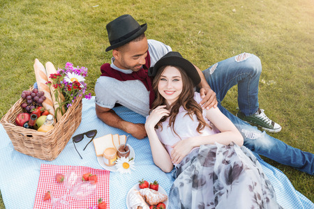 Relaxed young couple lying and having picnic on lawn Stock Photo