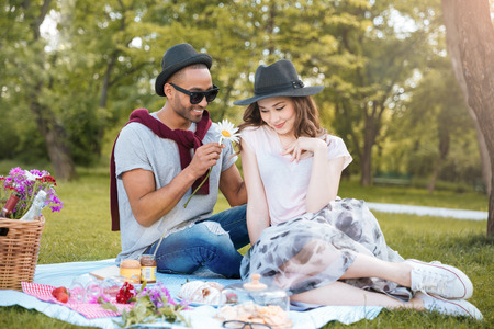 Smiling young man giving a flower to his girlfriend on picnic in park Stock Photo
