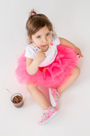 Image of little hungry children girl sitting over white background. Looking at camera eating chocolate dessert. Stock Photo