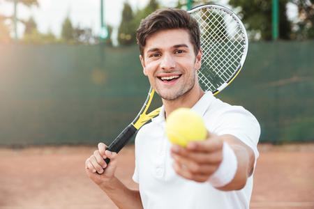 Uomo di tennis con la racchetta che dà palla. uomo così felice Archivio Fotografico - 84878612