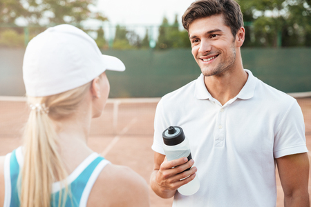 Beauty tennis couple on court. eyes to eyes. with water