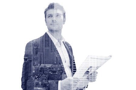 Double exposure of a  handsome young businessman with newspaper standing on the street Фото со стока