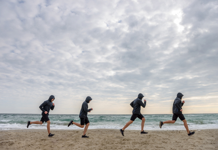 Multiple sport men clones in hoodies jogging at the beach in the morning