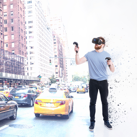 Image of handsome bearded man wearing virtual reality device standing over white background while holding joysticks in hands.