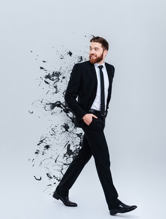 Full length portrait of a smiling bearded businessman in black suit walking and looking away with special effects Stock Photo
