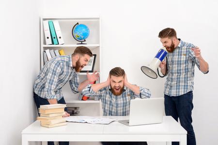 Hombre de negocios barbudo joven que trabaja con múltiples clones de sí mismo en la oficina, gritando y gritando en megáfono