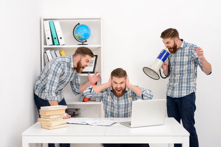 Young bearded business man working with multiple clones of himself at the office, shouting and yelling in megaphone