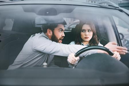 Geïrriteerde vrouw en man in auto. vooraanzicht. vrouw aan het stuur