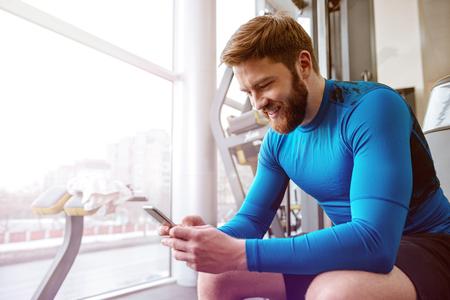 陽気な若いスポーツマン ジムで座っていると、携帯電話を見てのイメージ。 写真素材
