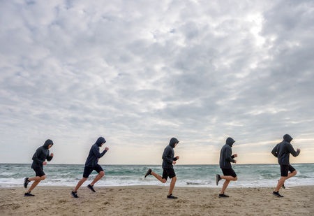 Multiple sport men clones jogging at the beach in the morning Reklamní fotografie