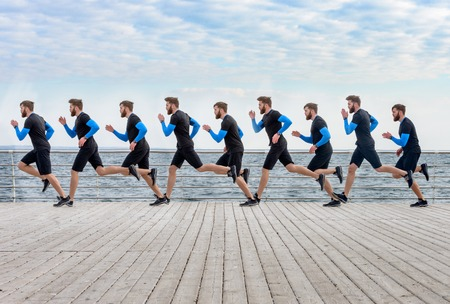 Portrait of a running one men clones on the wooden surface at the beach Reklamní fotografie