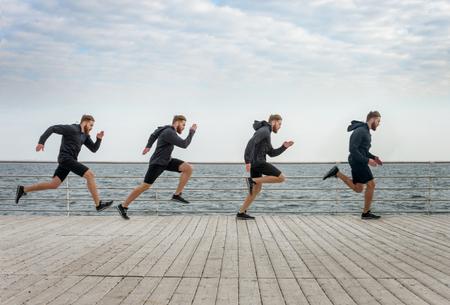 Four men clones running in sports wear along seaside on a wooden surface
