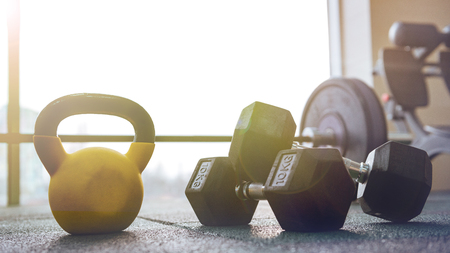 Photo of sport equipment in gym. Dumbbells on floor. Reklamní fotografie