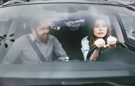 Vrouw en man in de auto. meisje achter het stuur. man op zoek naar de vrouw